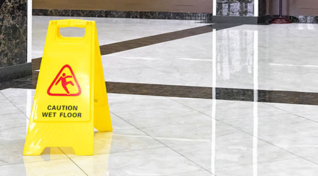 Marble shiny floor in luxury hall of hotel or office during cleaning. Panorama of washed cleaned floor and sign of caution. Professional care, maintenance and cleaning service of commercial interior.